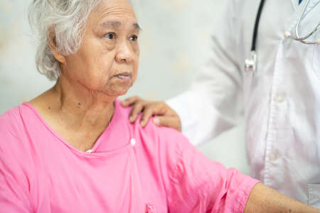 Asian doctor touching Asian senior or elderly old lady woman patient with love, care, helping, encourage and empathy at nursing hospital ward, healthy strong medical concept.