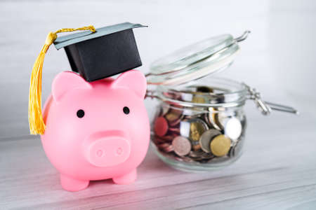 Save money coins in grass jar with piggy bank and graduation cap, Business finance education concept.