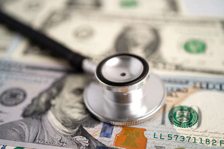 Stethoscope on US dollar banknotes, finance, account, statistic, analytic economy Business concept.