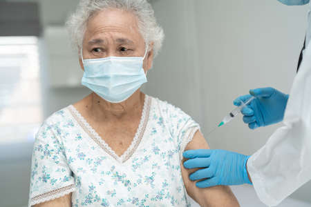 Elderly Asian senior woman wearing face mask getting vaccine by doctor make injection.
