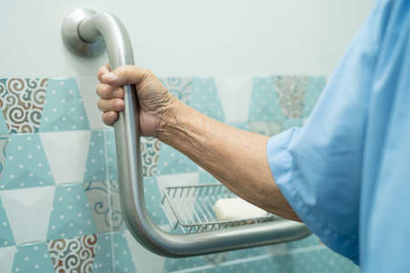 Asian senior or elderly old lady woman patient use slope walkway handle security with help support assistant in nursing hospital ward, healthy strong medical concept.