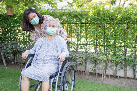 Help Asian senior or elderly old lady woman on wheelchair and wearing a face mask for protect safety infection Covid-19 Coronavirus in park. 免版税图像