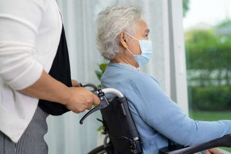 Help Asian senior or elderly old lady woman sitting on wheelchair and wearing a face mask for protect safety infection Covid-19 Coronavirus.