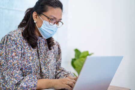 Asian lady businesswoman wearing mask for protect coronavirus to work from home communicate by conference video call on laptop, stay at home.