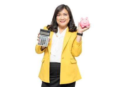 Business asian lady people in yellow suit holding calculator and piggy bank isolated on white background; finance economy banking saving concept.