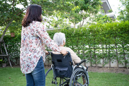 Help Asian senior or elderly old lady woman on electric wheelchair and wearing a face mask for protect safety infection Covid 19 Coronavirus in park 免版税图像