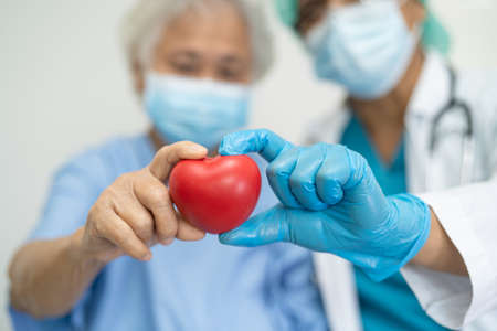 Doctor wearing ppe with mask give red heart for protect coronavirus to Asian senior or elderly old woman patient