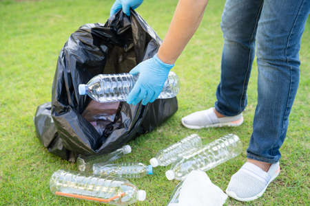 Asian woman volunteer carry water plastic bottles into garbage bag trash in park, recycle waste environment ecology concept. 免版税图像
