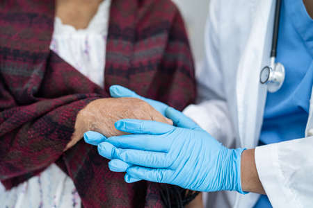 Doctor holding touching hands Asian senior or elderly old lady woman patient with love, care, helping, encourage and empathy at nursing hospital ward, healthy strong medical concept