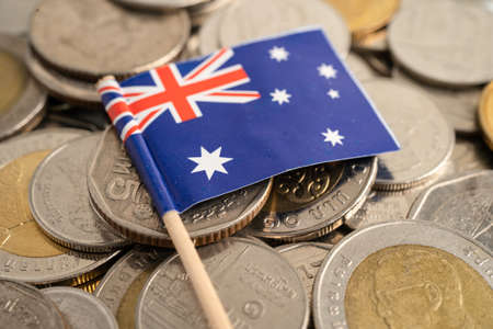 New Zealand flag on coins background, finance and accounting, banking concept.