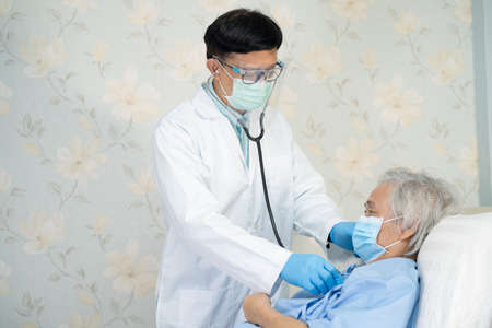 Asian doctor team check old senior lady patient for disease to motivation new normal to treat infection at hospital ward.