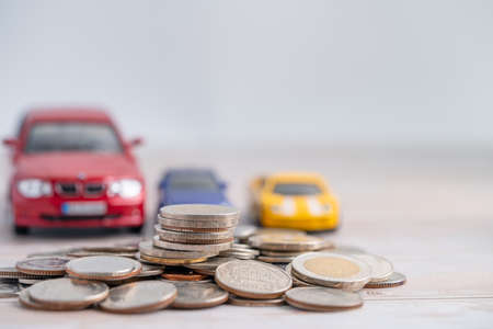 Car on coins background; Car loan, Finance, saving money, insurance and leasing time concepts.
