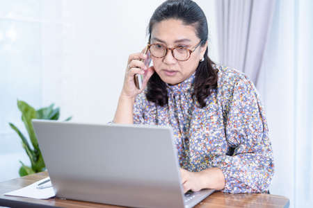 Asian lady businesswoman work from home communicate to office by conference video call on laptop, stay at home.