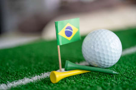 Golf ball with Brazil flag and tee on green lawn or grass is most popular sport in the world.