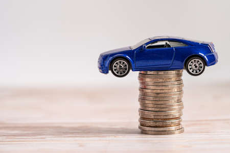 Car on stack of coins. Car loan, Finance, saving money, insurance and leasing time concepts. 免版税图像