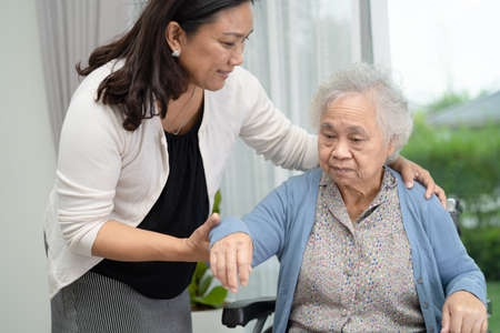 Help and care Asian senior or elderly old lady woman patient sitting on wheelchair at nursing hospital ward, healthy strong medical concept