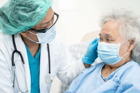 Doctor help Asian senior or elderly old lady woman patient wearing a face mask in hospital for protect safety infection