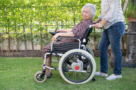 Doctor help and care Asian senior or elderly old lady woman patient sitting on wheelchair at park in nursing hospital ward, healthy strong medical concept. 免版税图像
