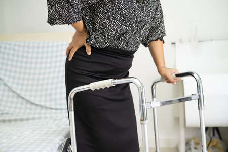 Asian lady patient pain her back wrist orthopedic lumbar with walker.