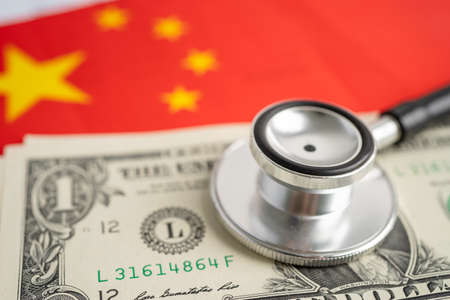 Black stethoscope on China flag background with US dollar banknotes, Business and finance concept. Фото со стока