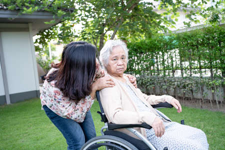 Help Asian senior or elderly old lady woman on electric wheelchair and wearing a face mask for protect safety infection Covid 19 Coronavirus in park Фото со стока