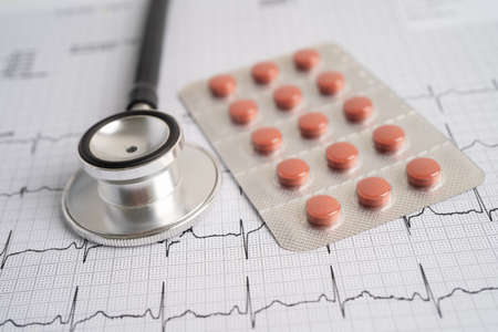 Stethoscope on electrocardiogram with capsule pill, heart wave, heart attack, cardiogram report.