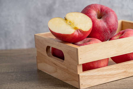Apple and half fruit in wooden box with copy space.