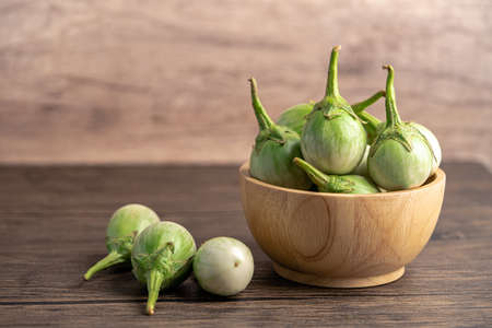Green eggplant fresh vegetable in wooden bowl with copy space.