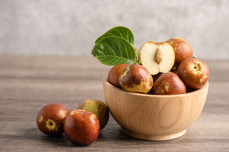 Jujube fruit or Chinese Dates in wooden bowl, healthy food. Фото со стока