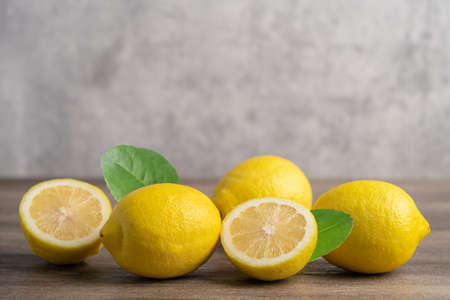 Lemon ripe fresh fruit with leaf on wooden background with copy space