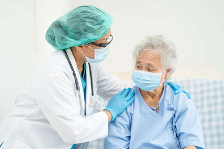 Doctor help Asian senior or elderly old lady woman patient wearing a face mask in hospital for protect safety infection and kill Covid-19 Coronavirus.