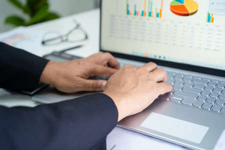 Asian accountant working and analyzing financial reports project accounting with chart graph in modern office, finance and business concept. Фото со стока