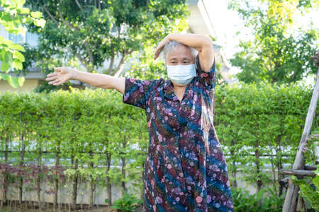 Asian senior woman with mask protect coronavirus exercise with happy in park, healthy strong medical concept