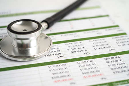 Stethoscope on spreadsheet paper, Finance, Account, Statistics, Investment, Analytic research data economy spreadsheet and Business company concept. Фото со стока