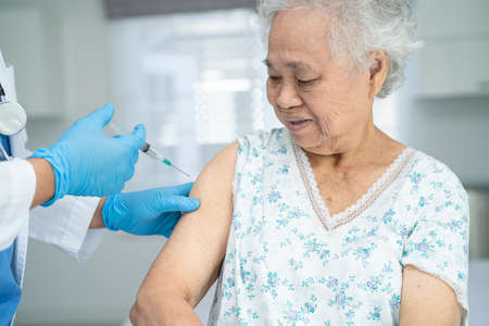 Elderly Asian senior woman wearing face mask getting covid-19 or coronavirus vaccine by doctor make injection. Фото со стока