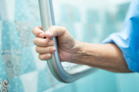 Asian senior or elderly old lady woman patient use slope walkway handle security with help support assistant in nursing hospital ward; healthy strong medical concept.