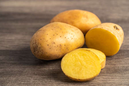 Potato raw and fresh vegetable food on wooden background. Фото со стока