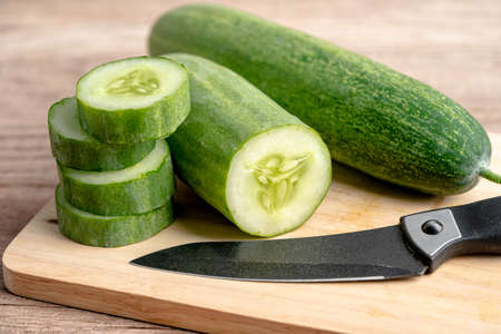 Cucumber vegetable food cut in slice and knife on cutting board for cooking in kitchen.