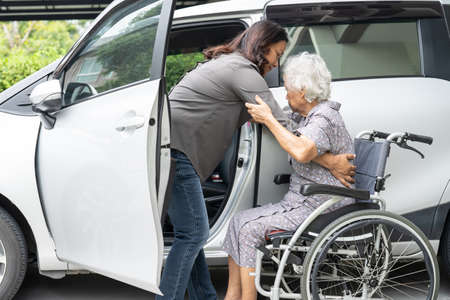 Help and support asian senior or elderly old lady woman patient sitting on wheelchair prepare get to her car, healthy strong medical concept. Фото со стока