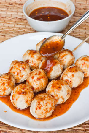 Roasted pork ball, pouring with sweet spicy sauce photo