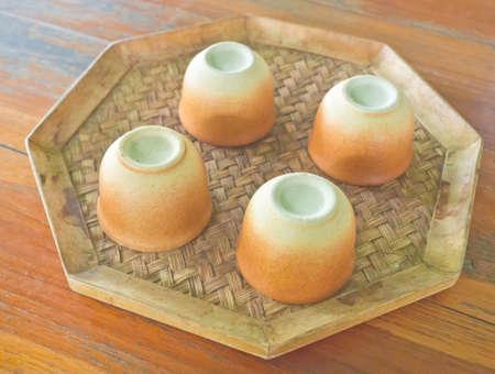 overturn: Rovesciare tazze di ceramica di bamb� intrecciati piattino Archivio Fotografico