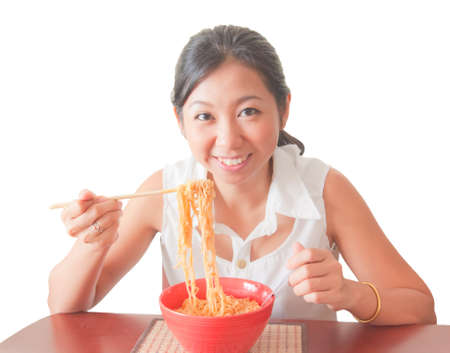An Asian woman eating noodles, isolated on white background photo