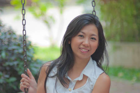 Portrait of an Asian woman relaxing on a swing photo