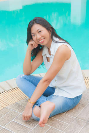 An Asian woman relaxing beside a swimming pool photo