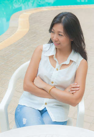 An Asian woman relaxing on a chair beside swimming pool photo