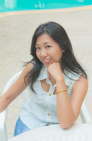 Portrait of an Asian woman sitting on a chair photo