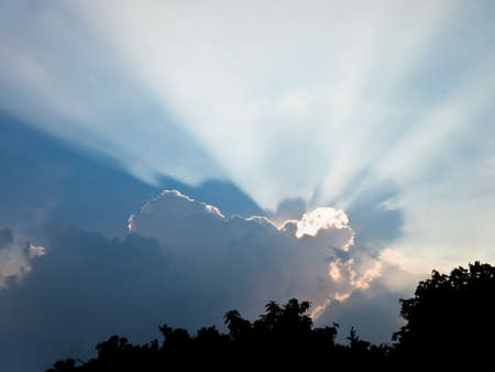 occur: Dramatic scattering sunlight from cumulus cloud in an evening twilight sky Stock Photo