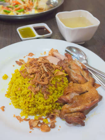 Khao Mok Gai-Thai style chicken biryani, Muslim halal yellow rice with chicken on white plate