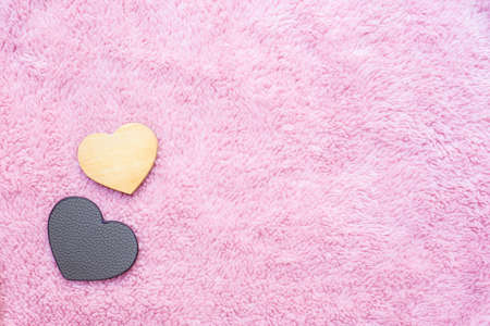 leather and wooden heart-shaped on pink artificial wool