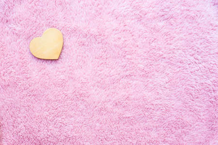 wooden heart-shaped on pink artificial wool